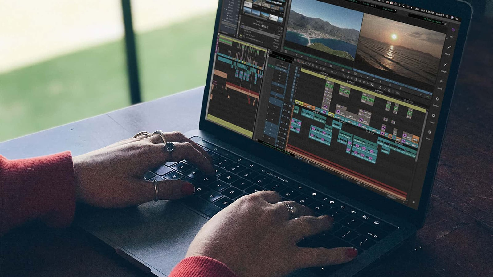 Hands on a laptop keyboard, we can see editing software open as someone works across a sunset over the sea and an arial shot of mountains.