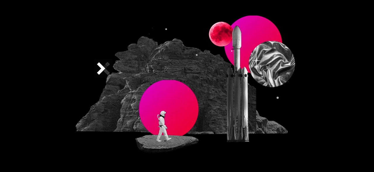 We see a space rocket and an astronaut walking infront of a neon pink coloured moon. We see rocks in the background and the xprize logo.