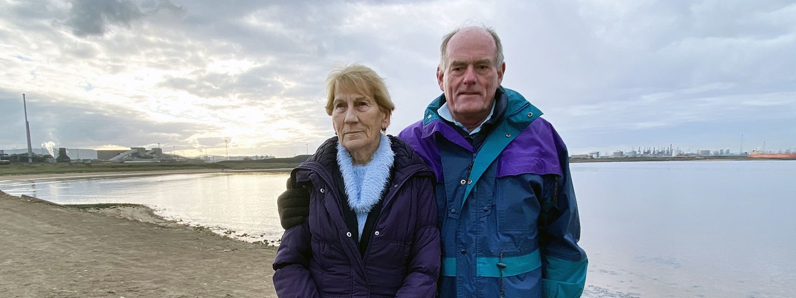 An elderly couple stand with arms around eachother in front of the sea, they look serious and concerned.