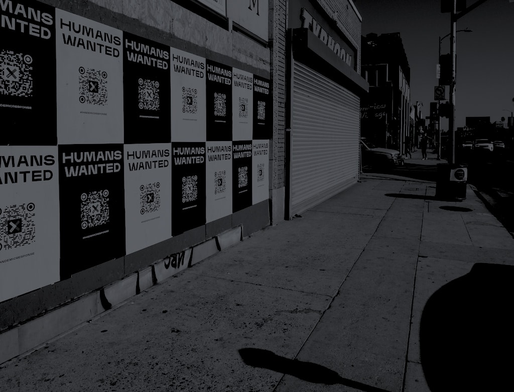 """In greyscale, posters up on a city wall, the posters feature QR codes and the text """"Humans Wanted"""""""