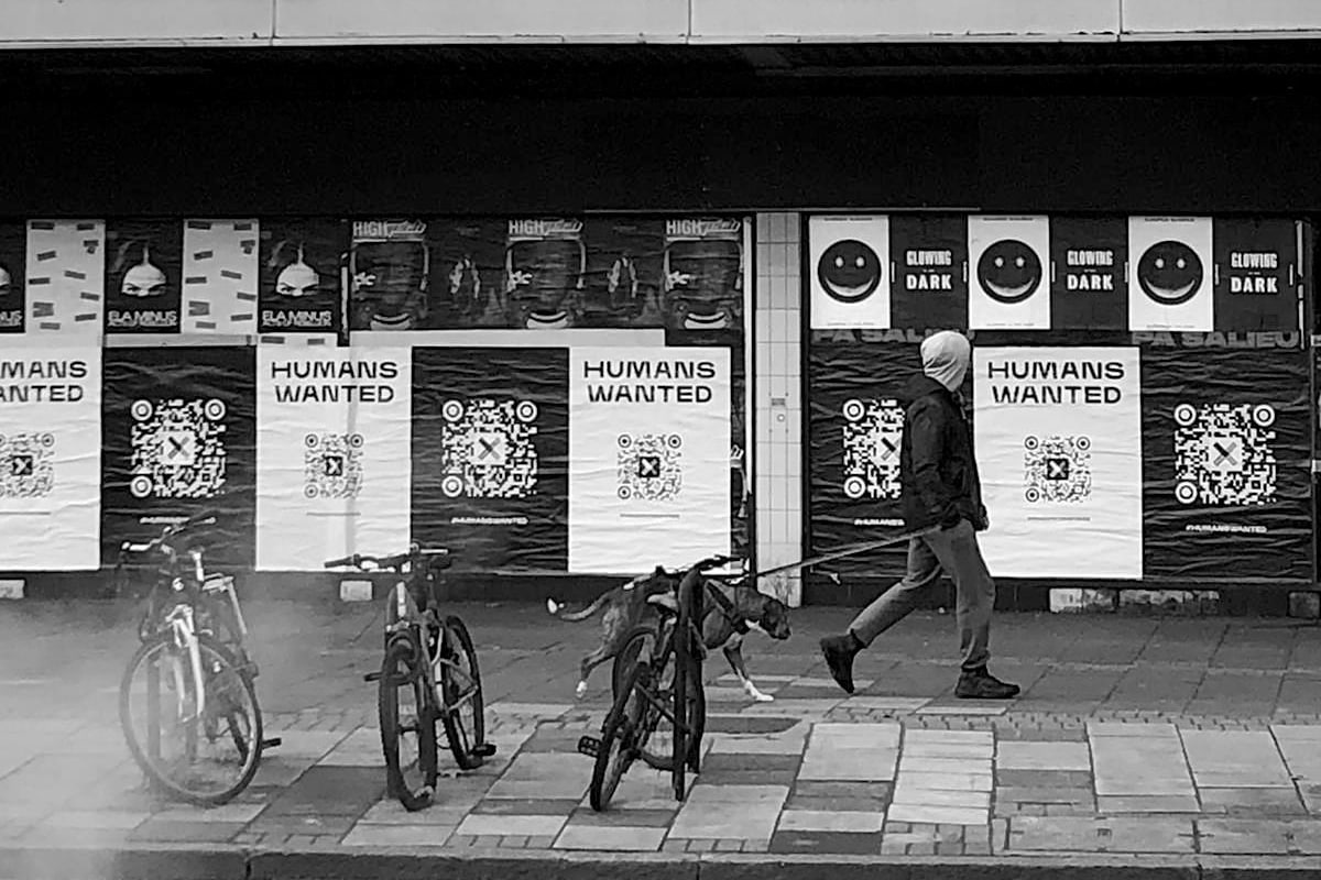 """In greyscale, a person and a dog walk past pasted up posters. There are 3 bikes in the foreground, the posters feature QR codes and the text """"Humans Wanted"""""""