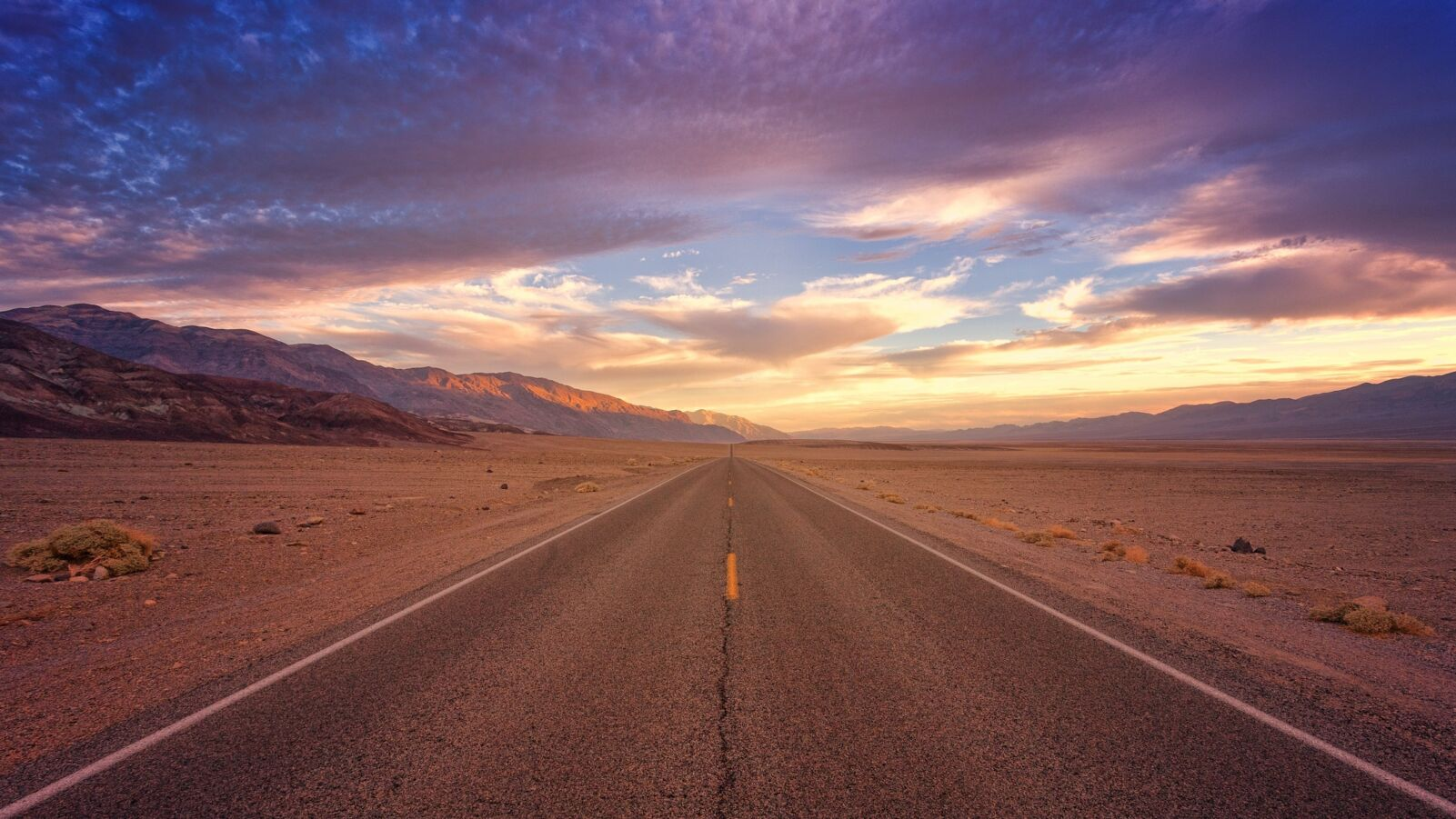 Wide angle image of yellow road leading through the desert to blue skies