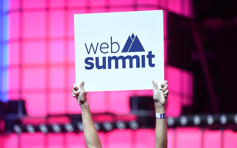 Hands hold up a white sign with the web summit logo on. The background is a pink tech style wall.